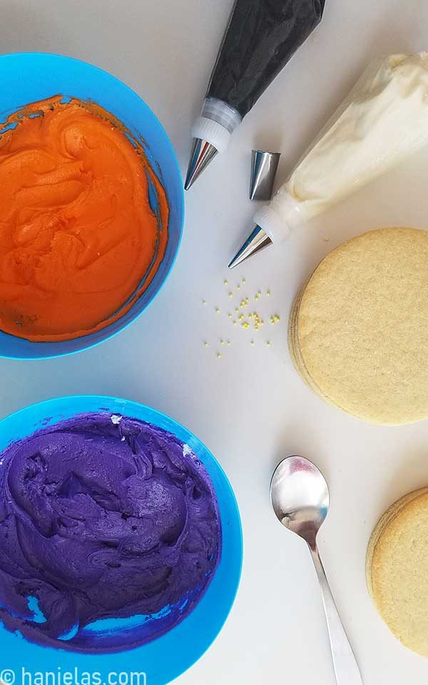 Orange and purple buttercream in bowls, piping bags filled with white and black buttercream on a kitchen counter.