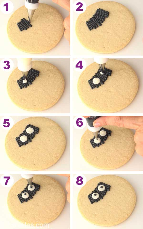 Piping black buttercream onto a round cookie, piping eyes onto the black buttercream.