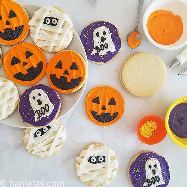 Round cookies decorated with orange, purple and white buttercream displayed on a plate.